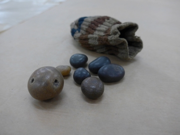 Image: Seven raven stones in a pouch.